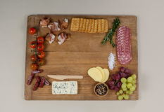 Roquefort cheese, biscuits and ham with various ingredients on chopping board. Against white background Royalty Free Stock Photo