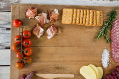 Roquefort cheese, biscuits and ham with various ingredients on chopping board. Against white background Stock Images