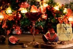 Roquefort del formaggio con i fichi, i dadi e un bicchiere di vino di vino rosso sopra immagini stock
