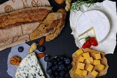 Roquefort, DorBlu, camembert and other cheeses with bread, tasting with berries, nuts, snack, big size resolution. Food banner for stock image