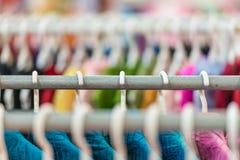 Ror av färgrik kläder på hängare på shoppar. Royaltyfri Fotografi