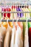 Ror av färgrik kläder på hängare på shoppar. Arkivbilder