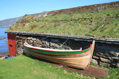 Rorbu with grass on the roof and old boat Royalty Free Stock Photos