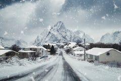 Rorbuer nevado da cidade com o blizzard que neva na maneira na vila fotografia de stock