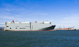 Roro vessel. Tug boat tugging a big vessel Royalty Free Stock Images