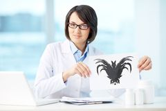 Rorschach test. Smiling psychologist showing paper with Rorschach inkblot Royalty Free Stock Image
