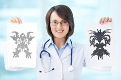 Rorschach test. Smiling psychologist showing papers with Rorschach inkblots Royalty Free Stock Photos