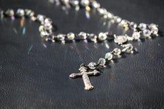 Rosário brilhante e bonito em uma superfície preta Transversal e saraiva Mary Pendant Foto de Stock Royalty Free