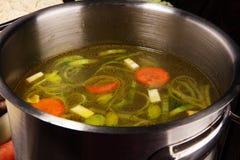 Rosół z marchewkami, cebul różnorodni świezi warzywa w garnku - kolorowa świeża jasna wiosny polewka Wiejski kuchenny sceneria ja zdjęcie royalty free