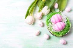 Rosa ägg för påsk i redet och de vita tulporna, kopieringsutrymme arkivbild