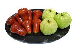 Rosa äpple och guavafrukt i den isolerade maträtten royaltyfri fotografi
