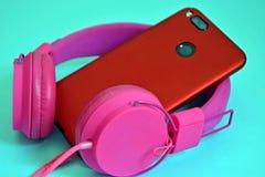 Rosa över huvudet yttre stor hörlurar och en telefon med en dubbelkamera i ett rött skyddande fall Closeup på en blå bakgrund royaltyfri foto