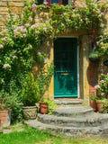 Rosa abschweifende Rose, die über grüner Tür des Steinhäuschens wächst Lizenzfreies Stockfoto
