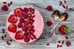Rosa acai, bunke för macapulversmoothie som överträffas med skivade jordgubbar, hallon och gojibär royaltyfri bild