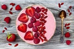 Rosa acai, maca Pulver Smoothieschüssel überstieg mit geschnittenen Erdbeeren, Himbeeren und goji Beeren Lizenzfreie Stockbilder