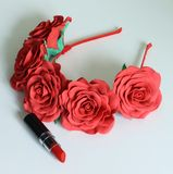 Rosa-accesorio rojo y un lápiz labial rojo en un fondo blanco Imagen de archivo