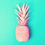Rosa ananas på en blå bakgrund Arkivfoto