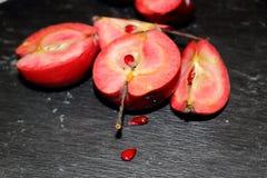 Rosa Apfel auf schwarzem Stein Stockfotografie
