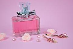 Rosa aromatisches Parfüm mit goldenen Haarnadeln auf Rosa Lizenzfreies Stockfoto