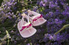Rosa Babyschuhe auf dem Lavendelgebiet Stockbilder
