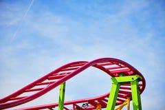 Rosa Bahnen der Achterbahn in einem Vergnügungspark Stockfotografie