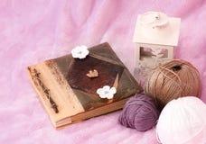 Rosa bakgrund med skeinen, boken och lyktan Royaltyfria Foton