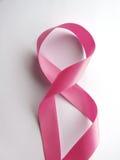 Rosa band mot cancer på vit bakgrund Arkivbild