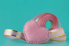 Rosa band och hjärta på rosa bakgrund Arkivbild