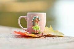 Rosa Becher mit Dekorationen in Form eines Mädchens in einem Kleid hergestellt Lizenzfreie Stockbilder