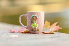 Rosa Becher mit Dekorationen in Form eines Mädchens in einem Kleid hergestellt Lizenzfreie Stockfotografie
