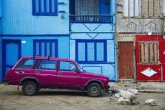 Rosa bil framme av gamla byggnader royaltyfri foto