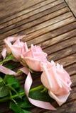 Rosa blühende Rosen auf Holz Stockfoto