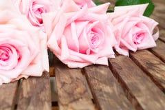 Rosa blühende Rosen auf Holz Lizenzfreies Stockbild