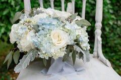 Rosa blanca y ramo azul de la boda de la hortensia en silla rústica con el fondo del verdor imagenes de archivo