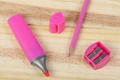 Rosa Bleistift, Leuchtmarker und Bleistiftspitzer auf hölzernem Schreibtisch Lizenzfreie Stockfotos