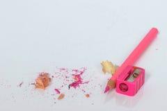 Rosa Bleistift und Bleistiftspitzer lokalisiert Stockbild