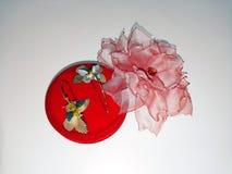 Rosa blomma som göras av hand-gjort tyg och guld- örhängen arkivbilder