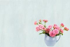 Rosa blommor i blå tillbringare på vattenfärgblått målade bakgrund Royaltyfri Fotografi