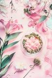 Rosa blomsterhandlareworkspace med liljor och annan blommar, den glass vasen med vatten Festlig framställning för blommaordningar Royaltyfria Bilder