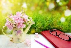 Rosa Blume, Leerseitenpapier und Bleistifte über grünem Gras der Natur im weichen Pastellton Stockfotografie