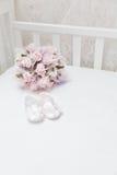 Rosa Blumen und die Sandalen der Kinder auf dem weißen Bett Lizenzfreie Stockfotografie