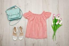Rosa blus, vita skor, handväska och en bukett av tulpan trendigt begrepp spelrum med lampa Royaltyfri Bild
