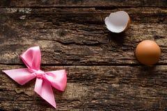 Rosa Bogen und Oberteile von den Eiern auf dem hölzernen Stockfotografie