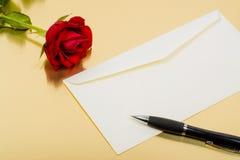 Rosa bonita do vermelho um envelope e uma pena em um fundo do ouro Imagens de Stock