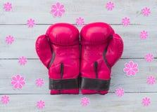 Rosa Boxhandschuhe und Blumen auf einem hölzernen Hintergrund, Draufsicht Lizenzfreies Stockfoto