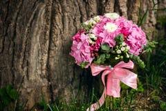 Rosa bröllopbukett med en rosa pilbåge Fotografering för Bildbyråer