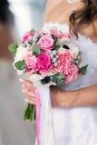 Rosa Brautblumenstrauß in den Händen Lizenzfreie Stockfotos