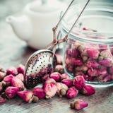 Rosa brota o chá, o infuser do chá, o frasco de vidro e o bule no fundo Fotografia de Stock Royalty Free