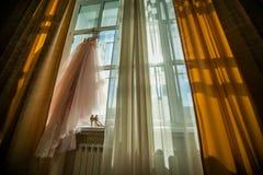 Rosa brudklänning på fönstret Arkivbild