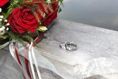 Rosa bukett med vigselringar Arkivbild